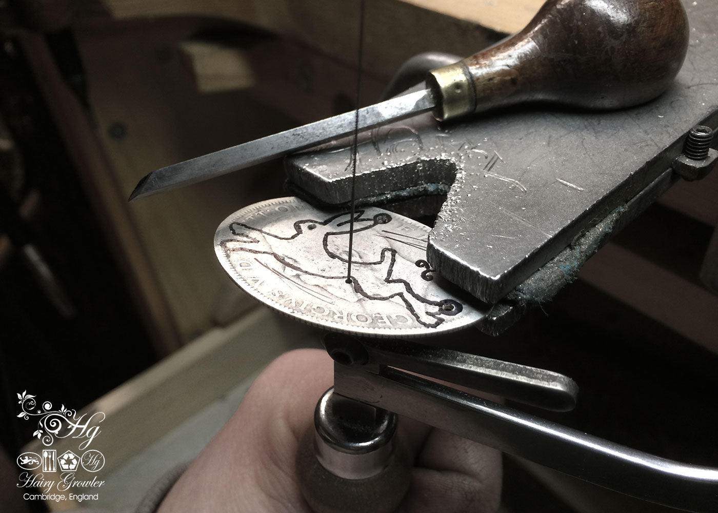 contemporary handmade artisan and upcycled sterling silver magical leaping hare necklace being cut out of the silver coin