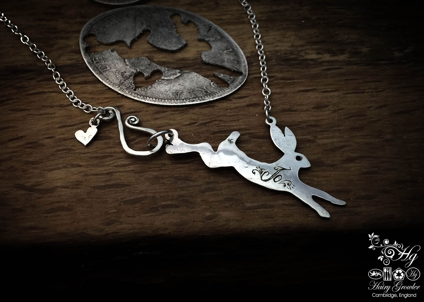 Handcrafted and recycled sterling silver magical leaping hare necklace being cut out of the silver coin