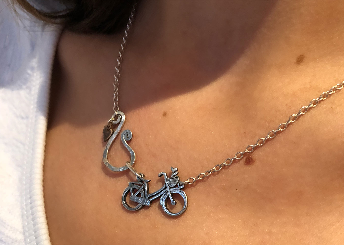 Bicycle necklace handcrafted and created with environmental awareness. Recycled silver coin jewellery made in Cambridge